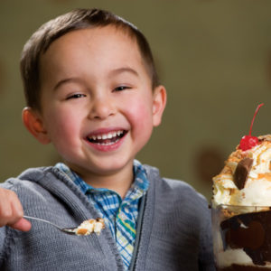 smiling boy eating a gooey ice cream
